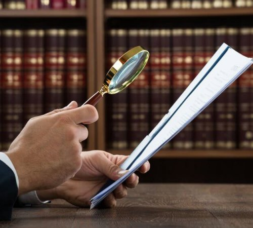 48227437 - cropped image of lawyer examining documents with magnifying glass in courtroom